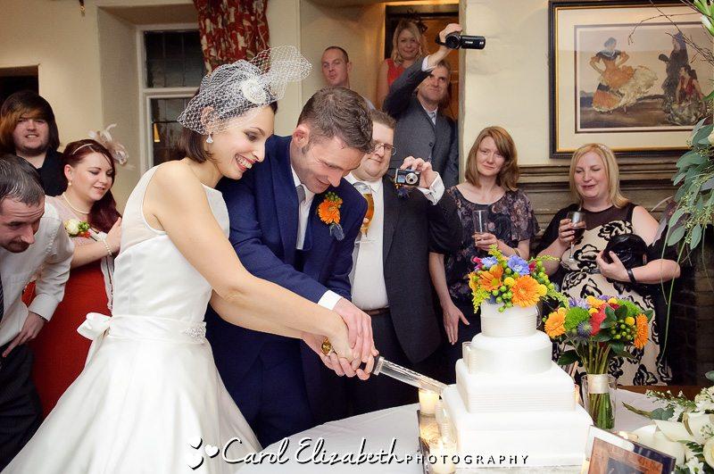 Bride and groom cutting their wedding cake in Bay Tree Burford wedding