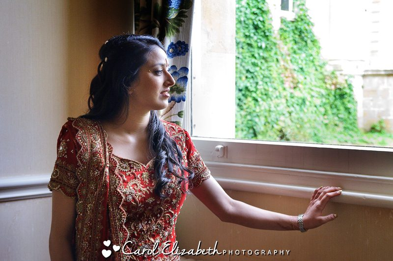 Bride at the window - Professional wedding photographer at Heythrop Park weddings