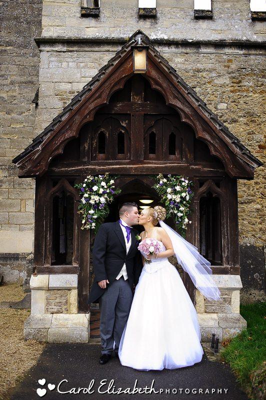 Bride and groom kissing outside Radley Church