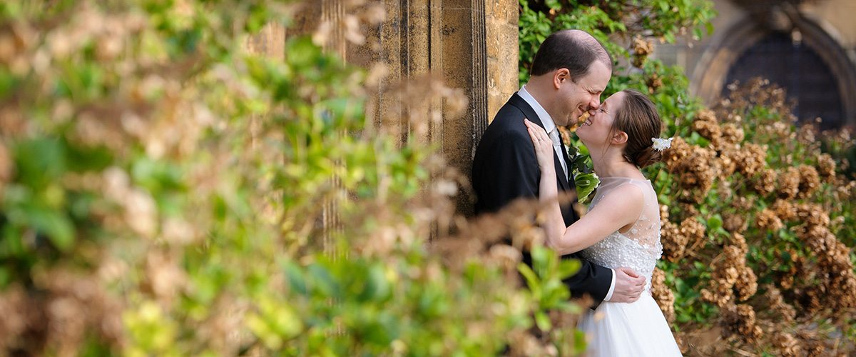 Marriage at Trinity College in Oxford - wedding couple kissing in the grounds of Trinity College