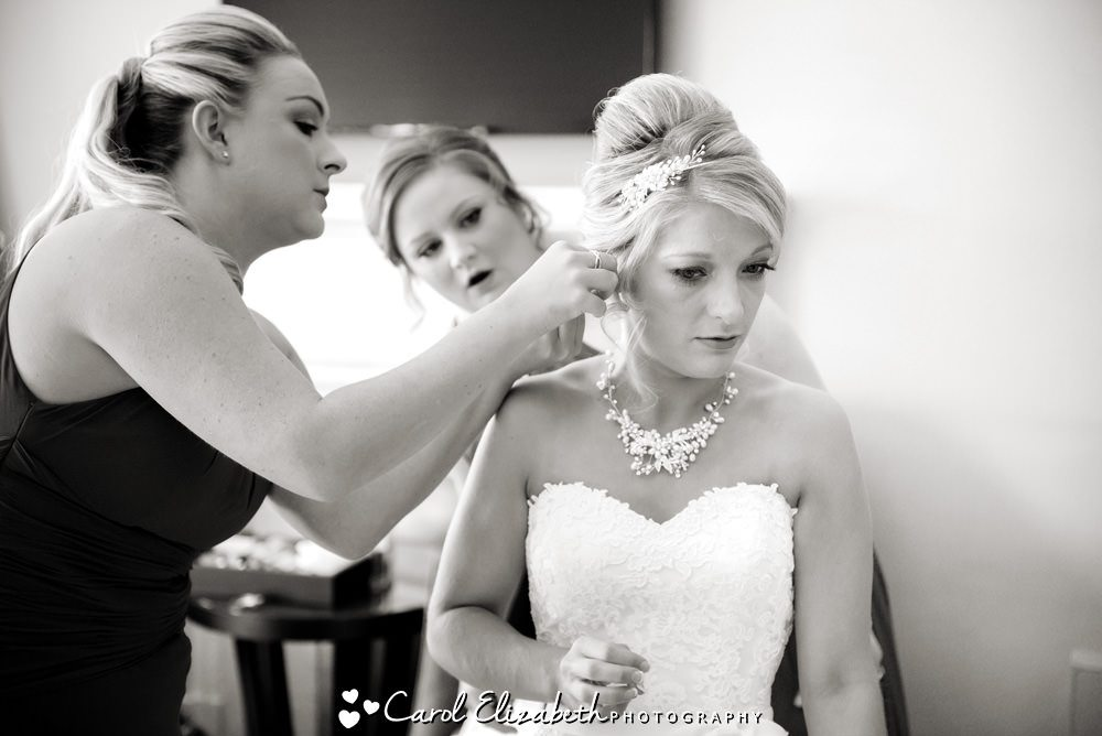 Bride putting on earrings at Milton Hill House Hotel wedding