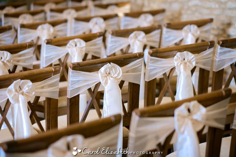 Wooden chairs with white ribbons