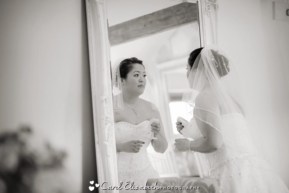 Bride looking in the mirror before wedding ceremony at Caswell House