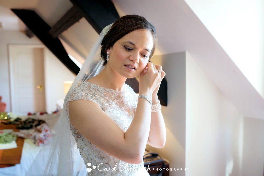 Bride putting on earrings
