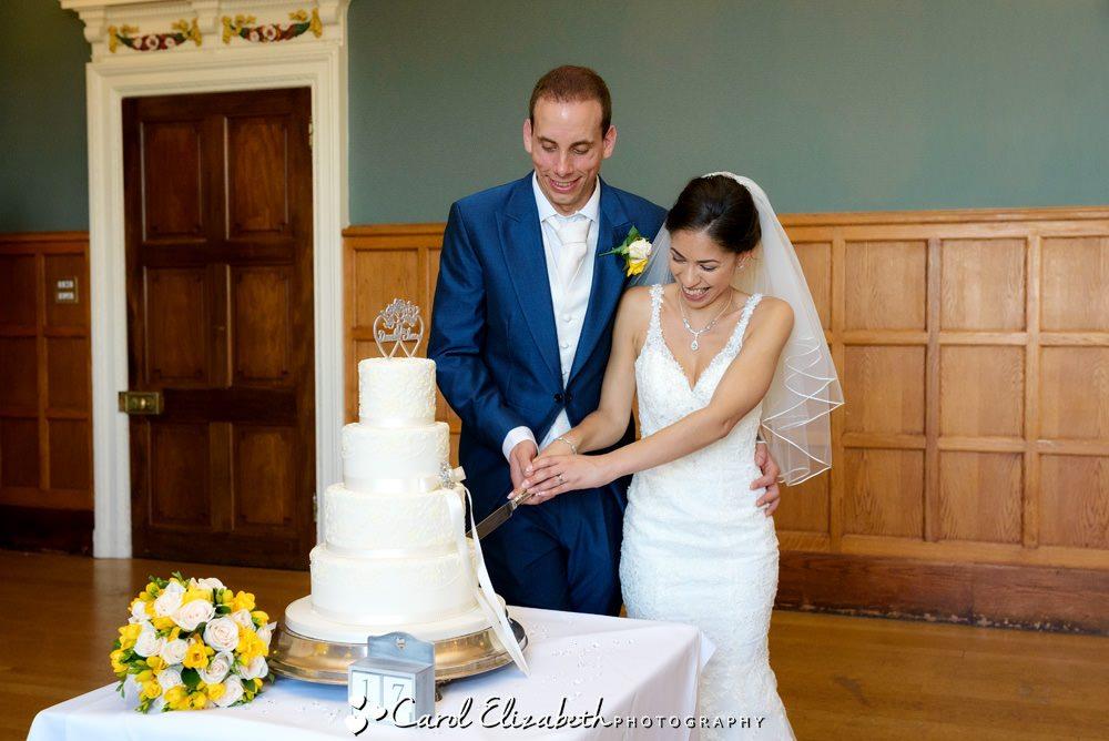 Cutting wedding cake at Eynsham Hall