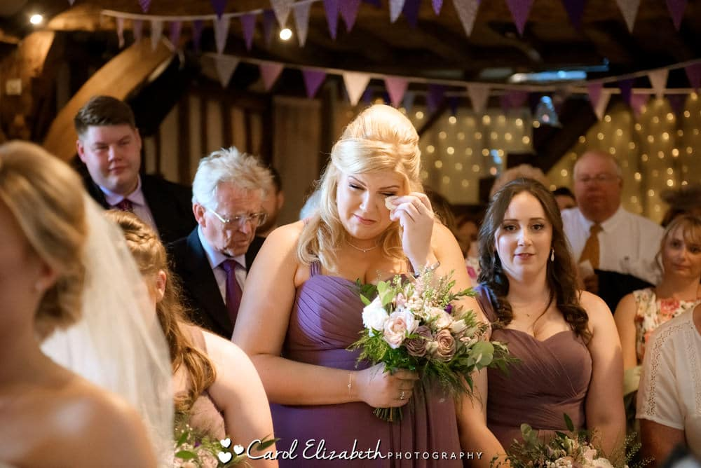 Bride wiping a tear during wedding