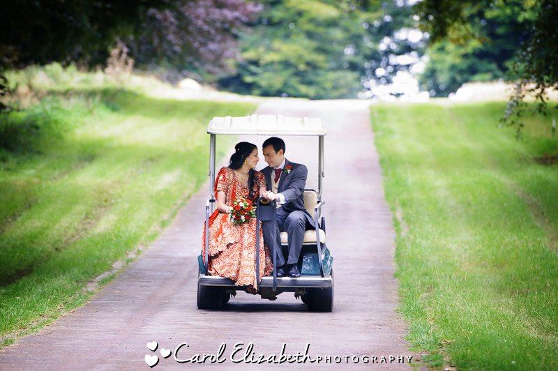 Wedding couple on golf buggy at Heythrop PArk wedding