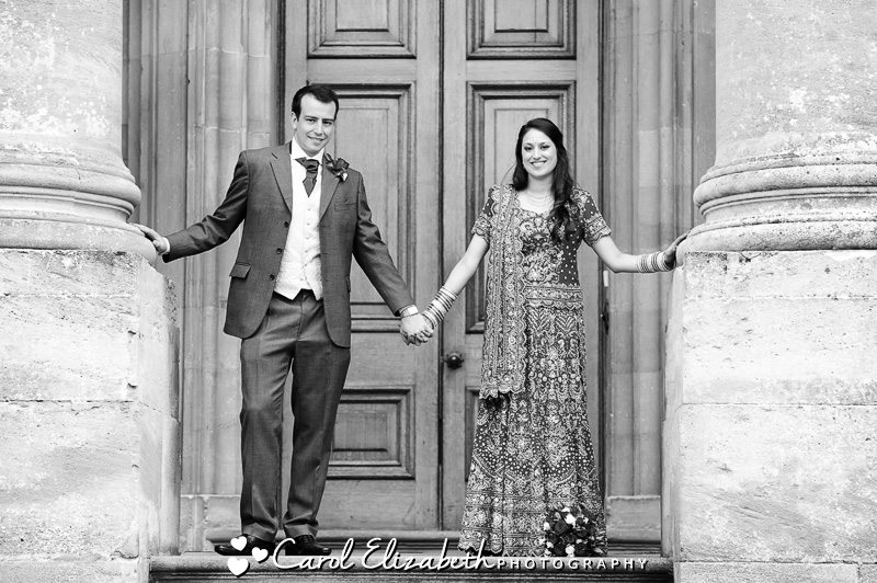 Bride and groom next to the pillars during Heythrop Park wedding