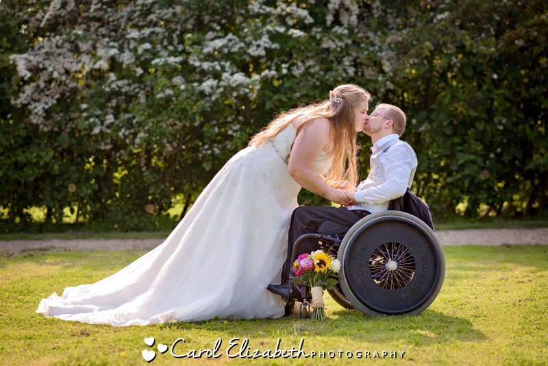 Wedding couple kissing wheelchair