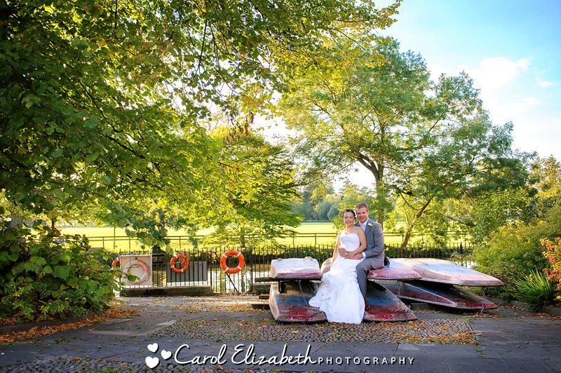 Bride and groom sitting on punts next to the river Thames