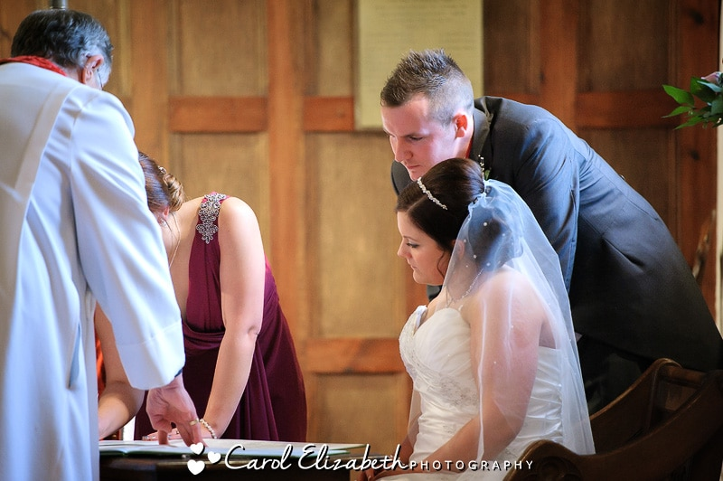 Signing the register - reportage wedding photography in Oxfordshire