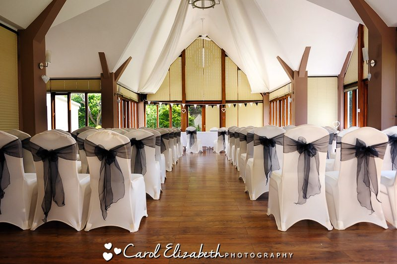 The wedding ceremony with white chairs and black sashes