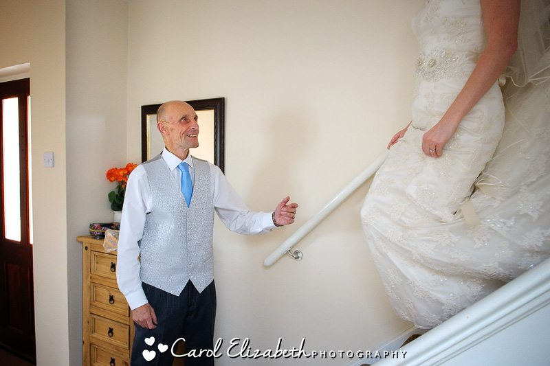 Dad helping bride down the stairs