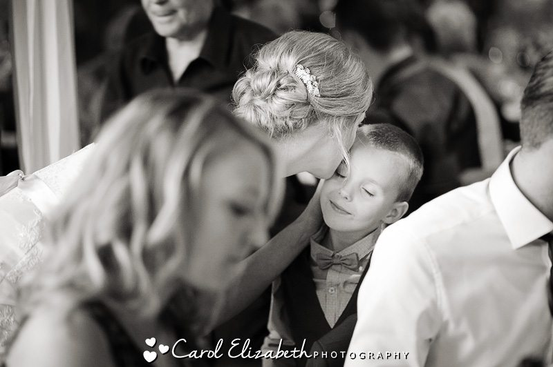 Informal wedding photo of bride kissing boy in black and white