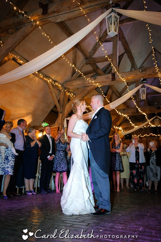 Bride and Groom dancing at Lains Barn wedding with twinkly lights in the background