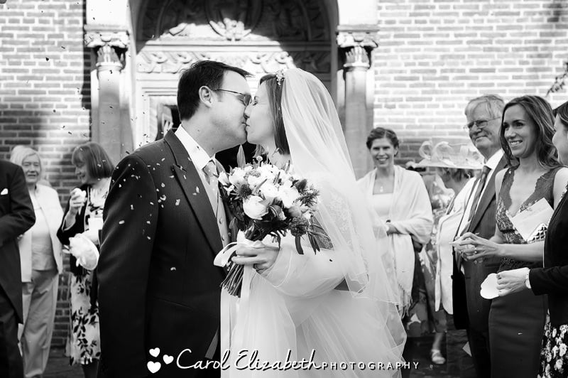 Kissing with confetti by Oxford wedding photographer