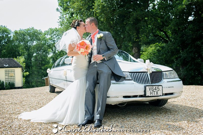 Fun bride and groom with car