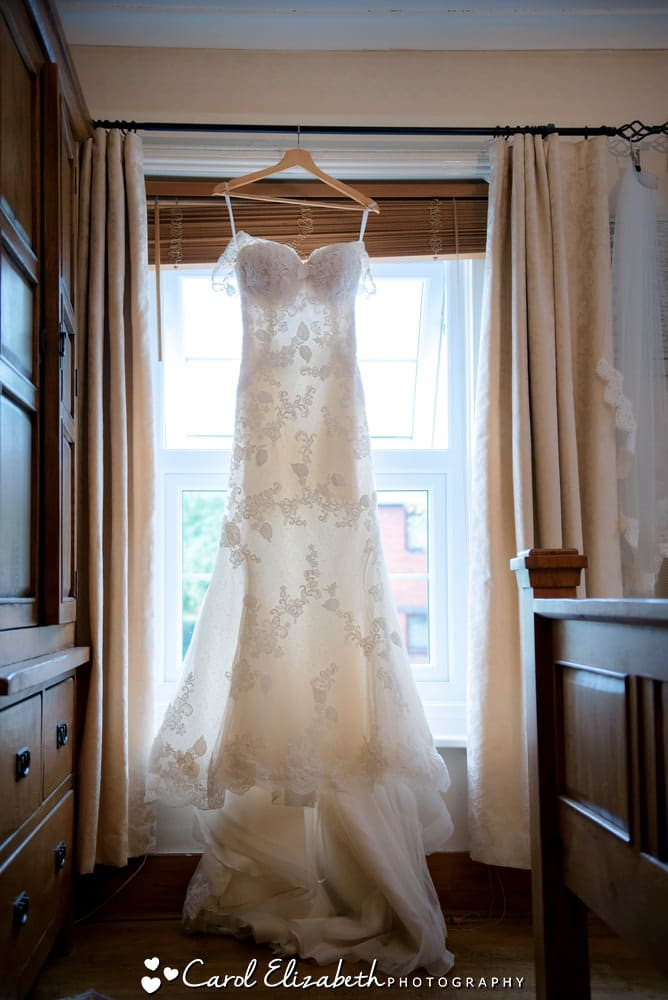 Lace wedding dress hanging in the window