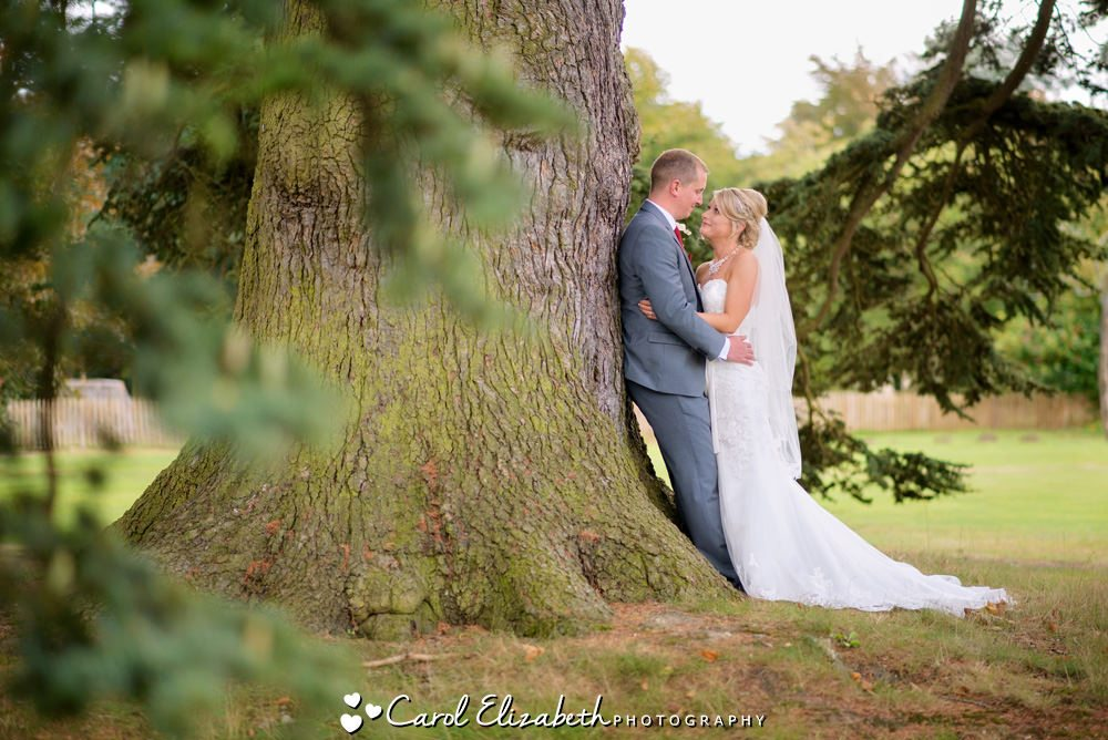 Bride and groom next to tree
