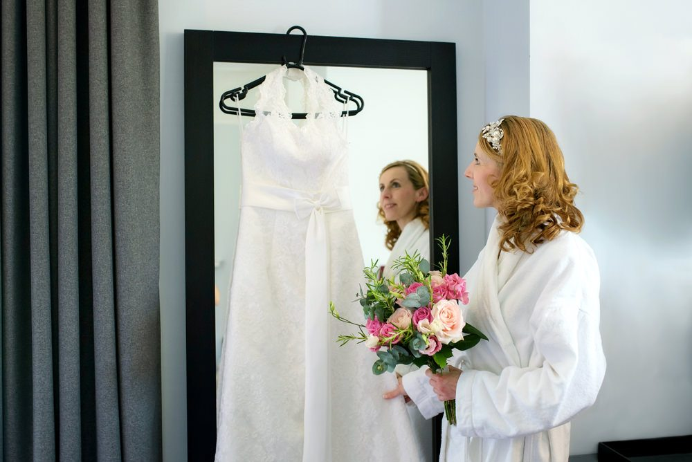 Bride looking at her wedding dress in the mirror