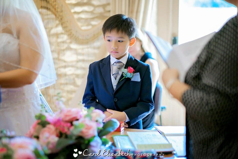 Young boy ring bearer with red rose