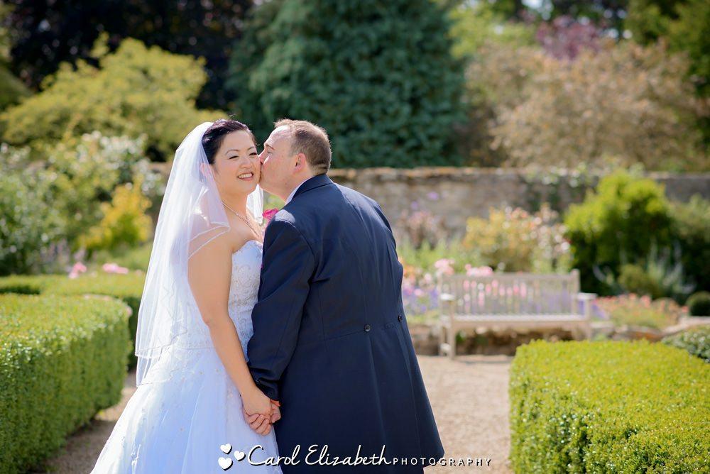 Groom kissing bride on the cheek