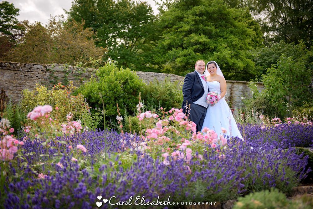 Bride and groom in the flower garden at Caswell House in Oxfordshire