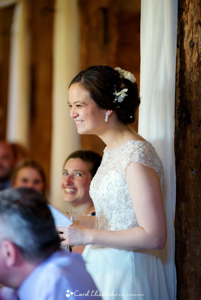 The bride smiles whilst giving a speech at Lains Barn