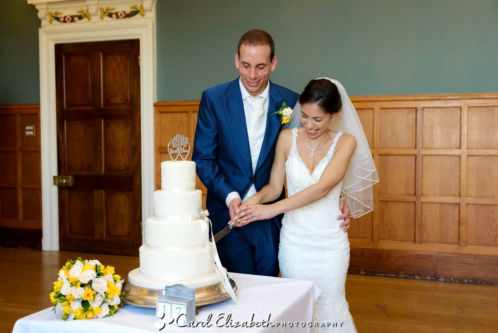 Cutting wedding cake at Eynsham Hall