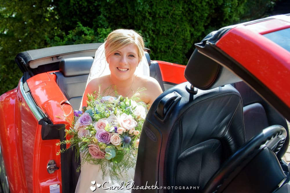 Bride arriving in a red car