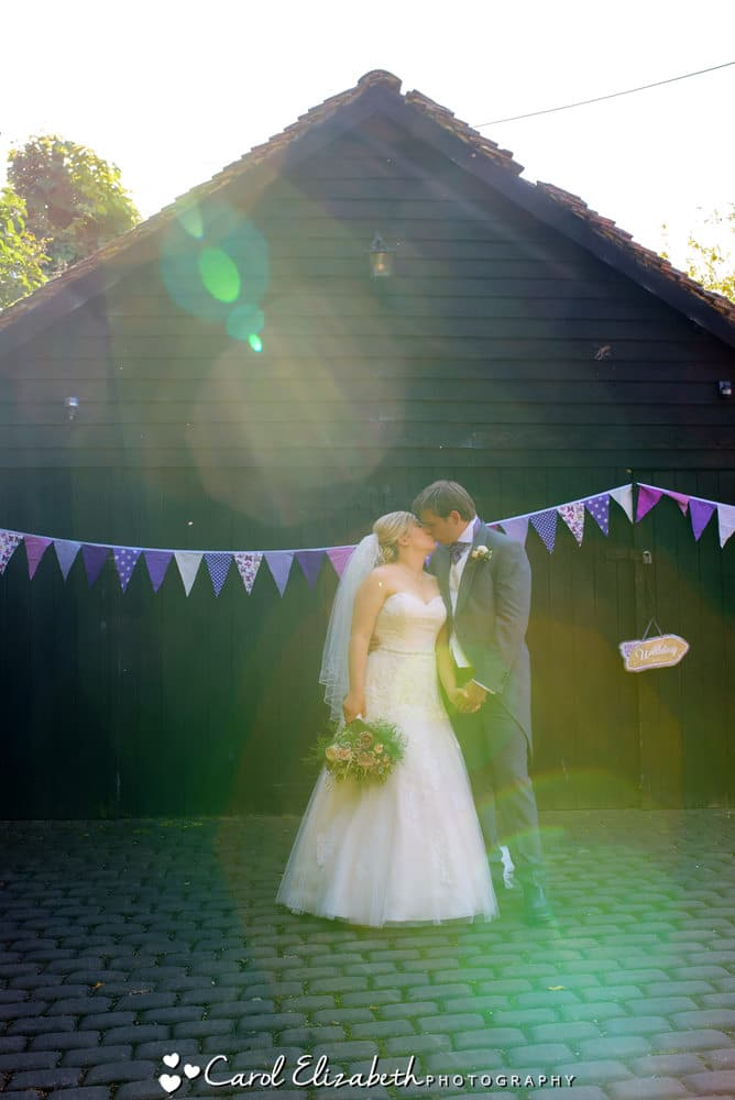 Bride and groom kissing - sunflare