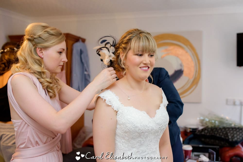 Bridesmaid putting on necklace