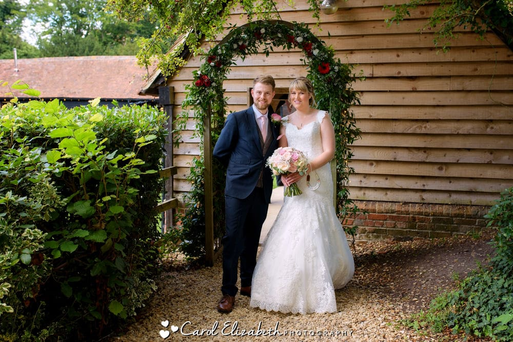 Wedding couple under the archway at Lains Barn