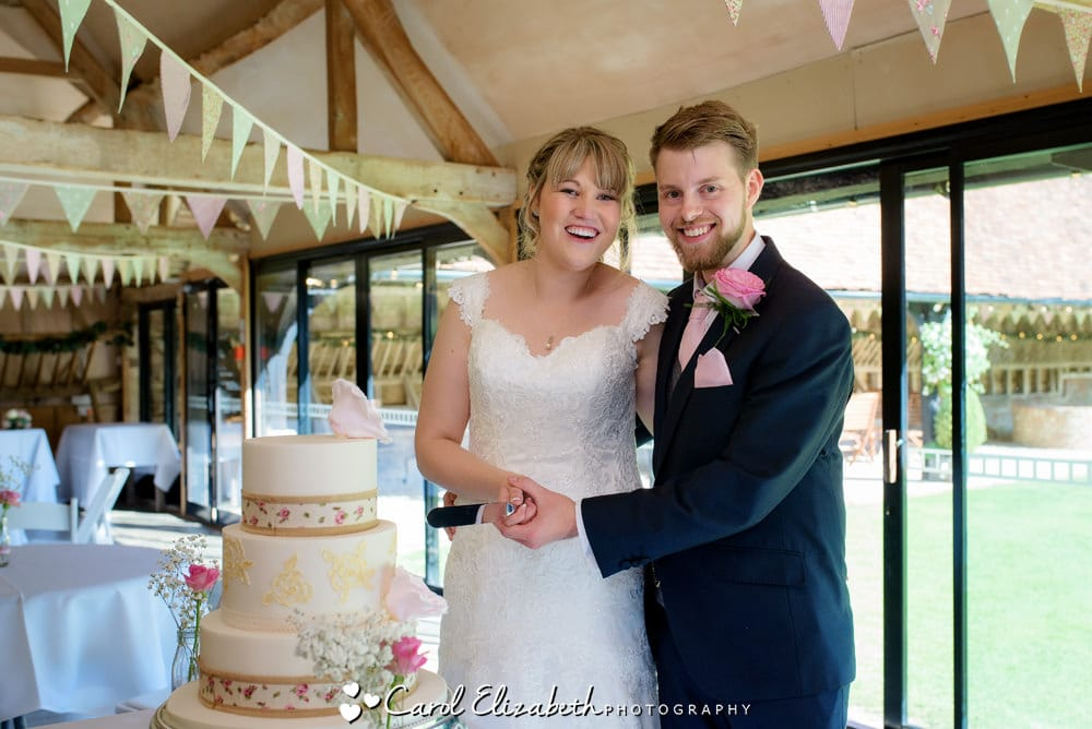 Cutting the cake at Lains Barn wedding