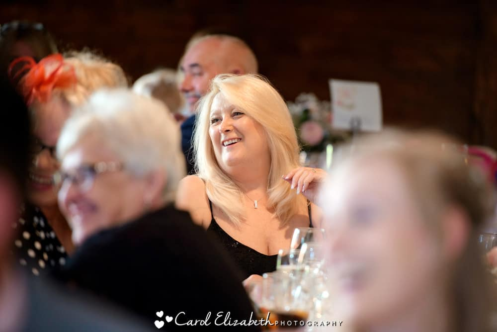 Guests smiling during wedding speeches