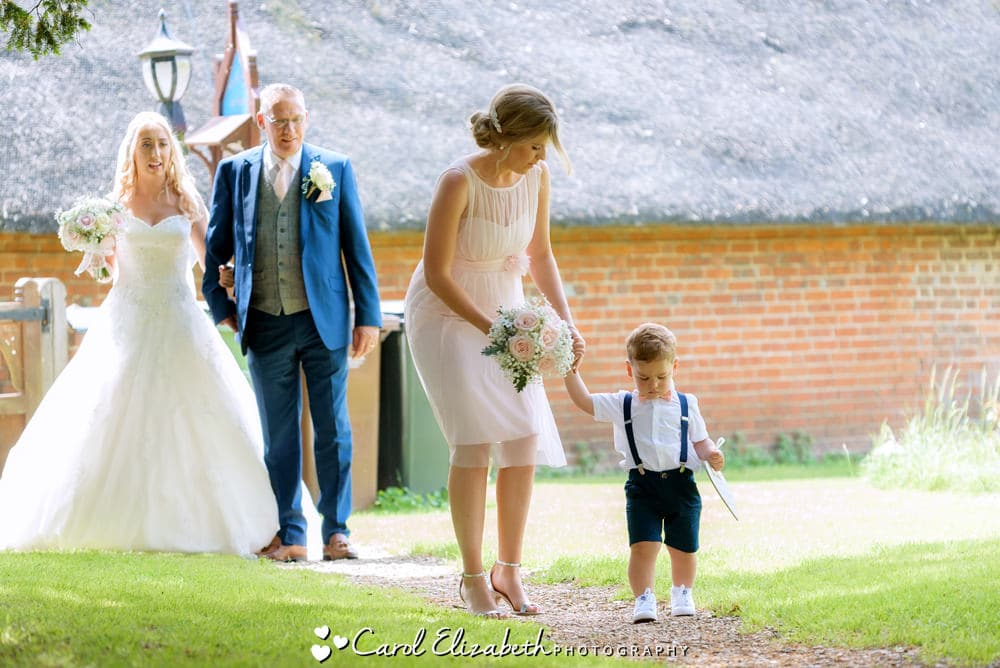 Reportage photo of bride and pageboy arriving at the church