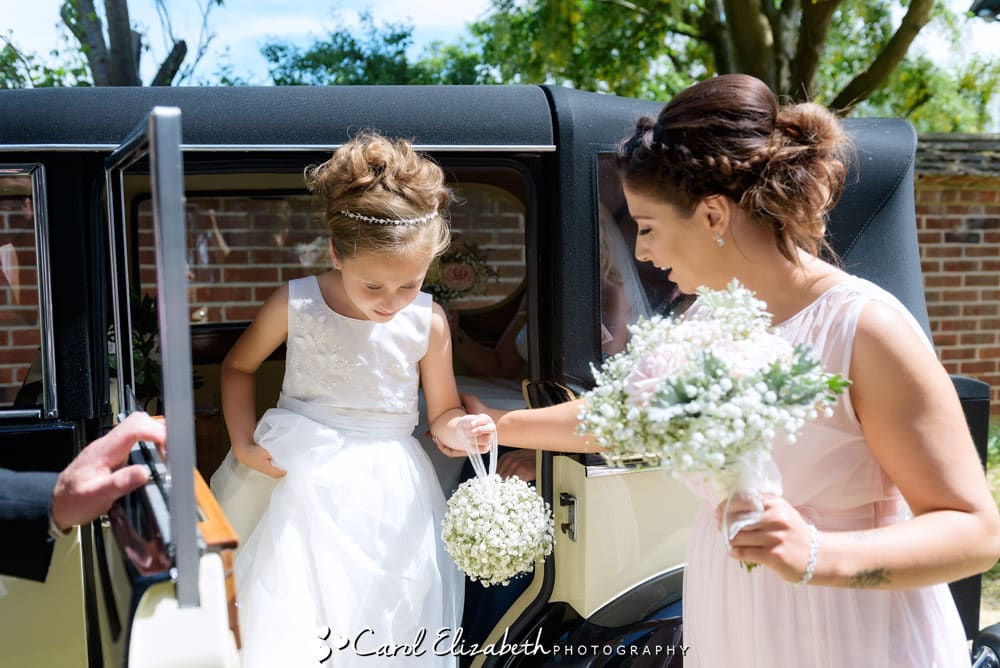 Bridesmaid getting out of a vintage wedding car