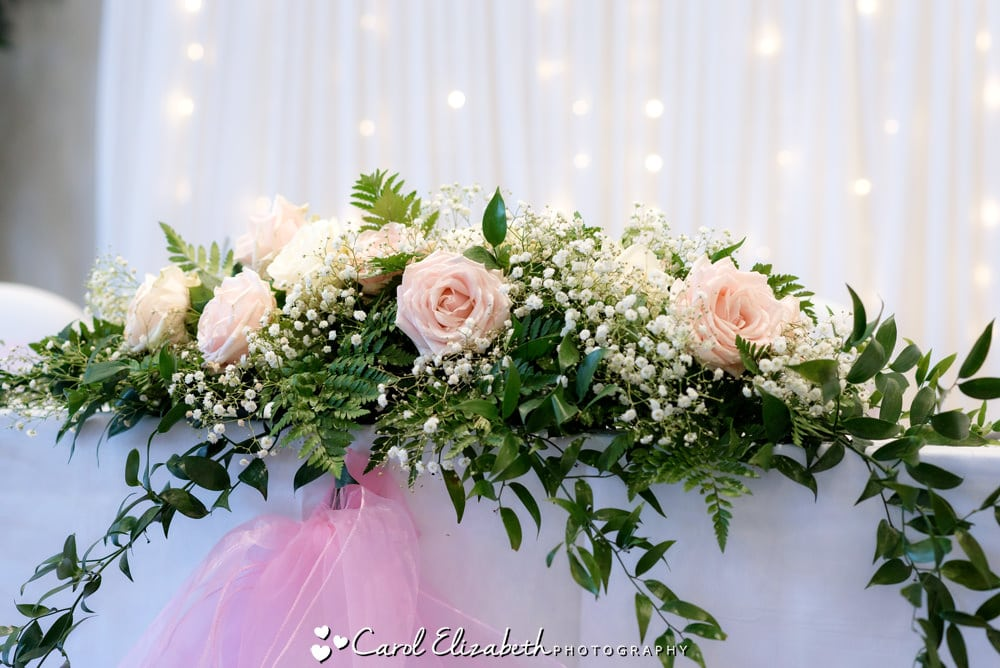 Pink roses wedding flowers on the top table with fairy light backdrop