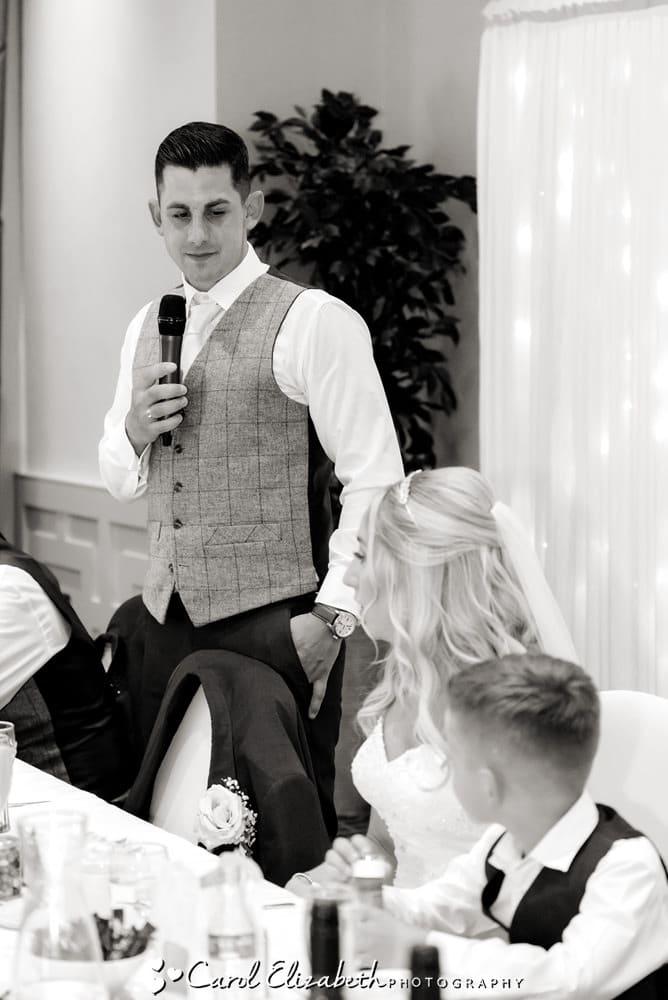 Groom giving wedding speech looking at bride