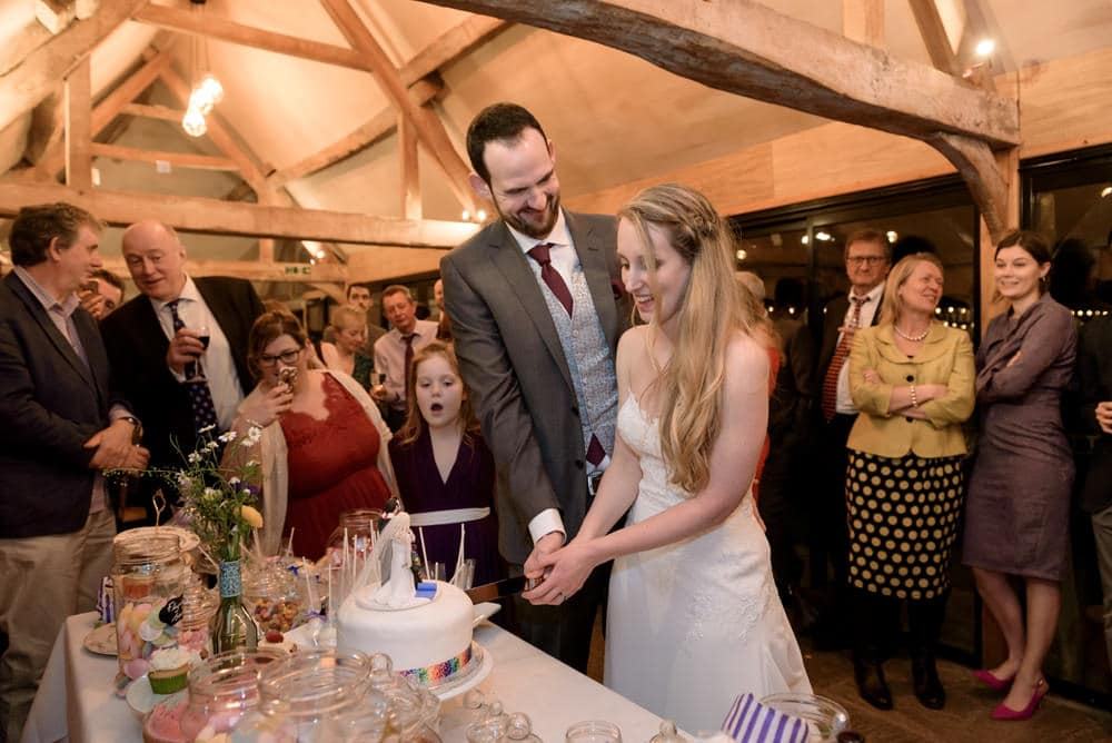 Cutting the wedding cake at Lains Barn wedding