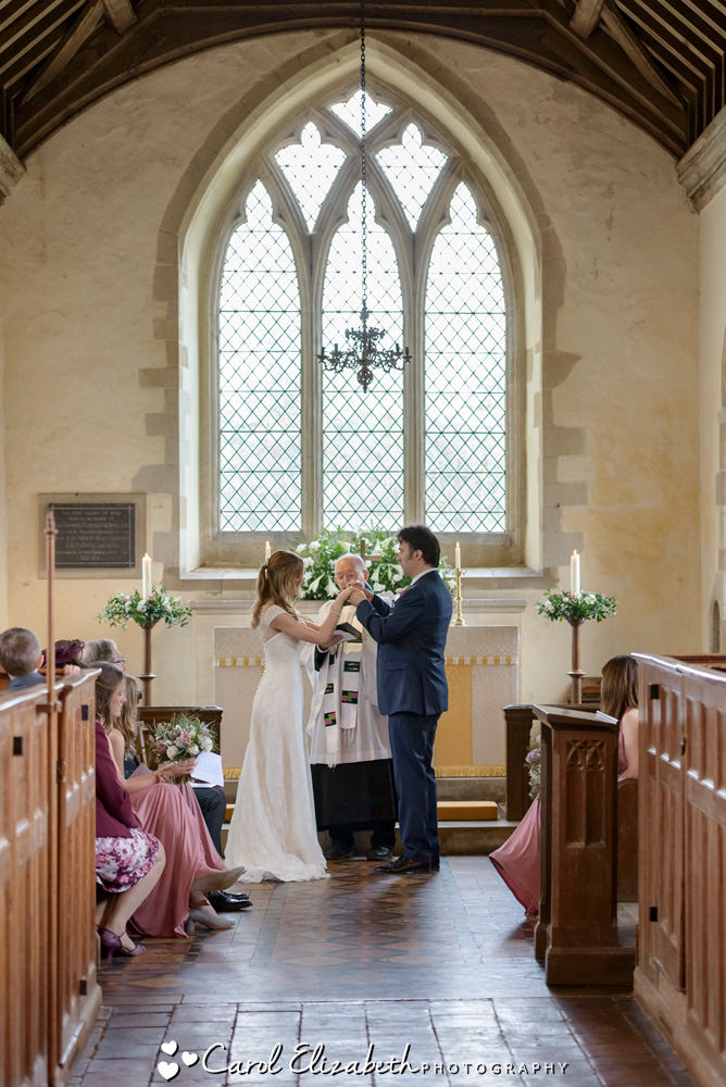 Wedding photographer at Nether Winchendon Church - bride and groom with full length window