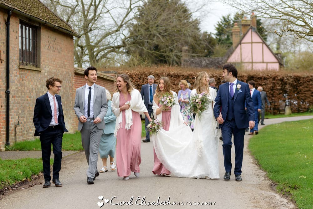 Wedding party walking to Nether Winchendon House from the church