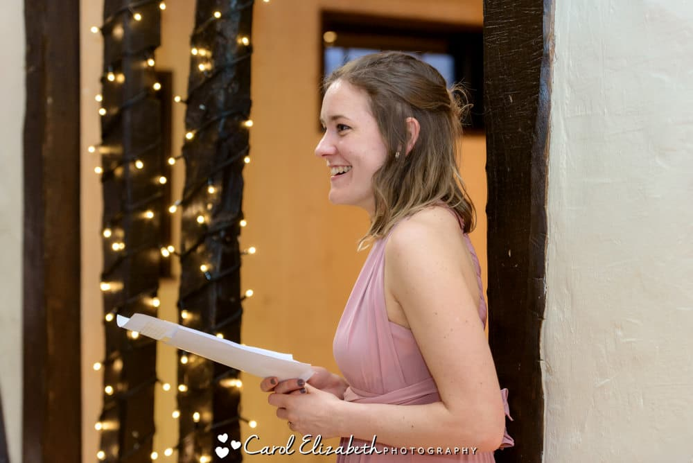 Bride giving a speech at wedding reception with fairy lights