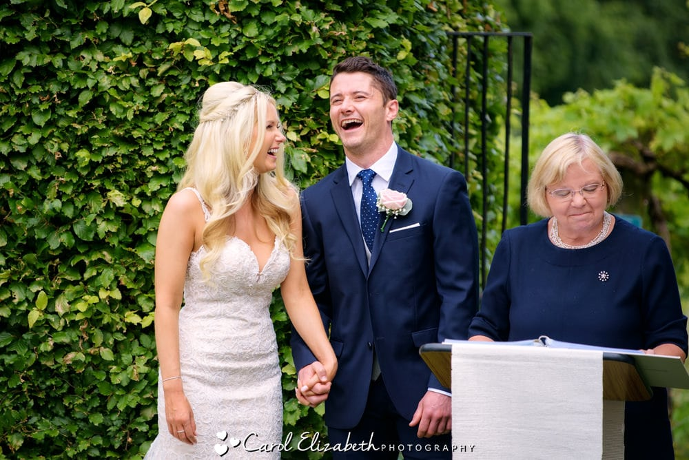 Laughing bride and groom during wedding service - wedding photographer in Oxfordshire