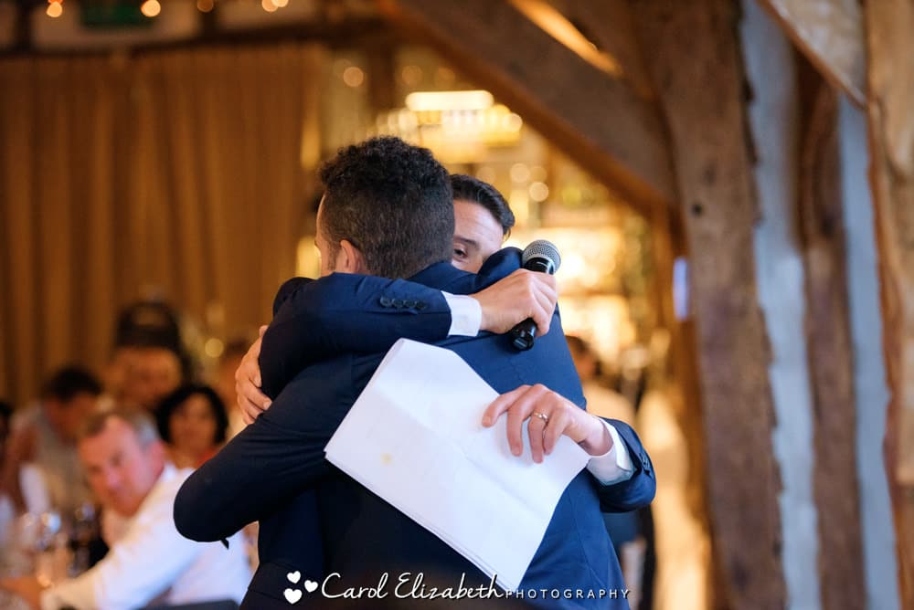 Groom and best man hugging during speeches