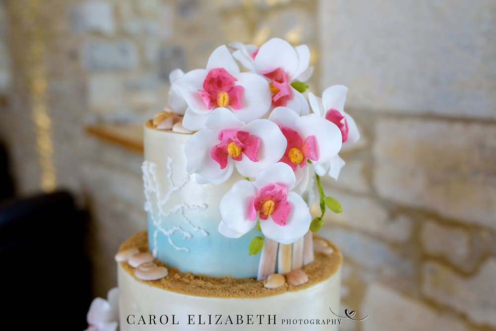 Beach theme wedding cake with flowers and sand