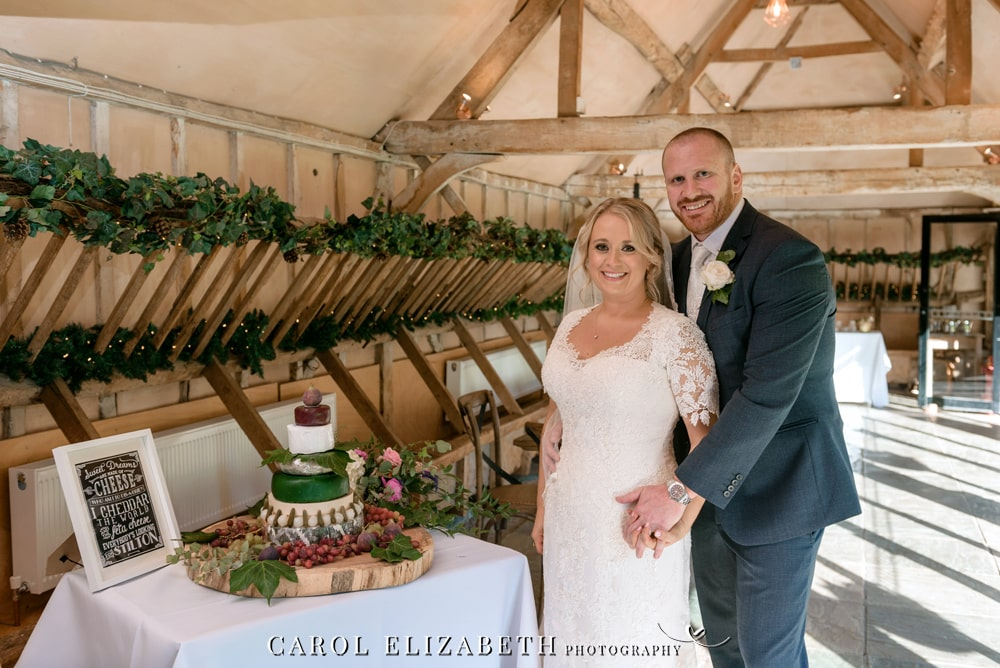 Cutting the wedding cake at Lains Barn wedding venue in Oxfordshire