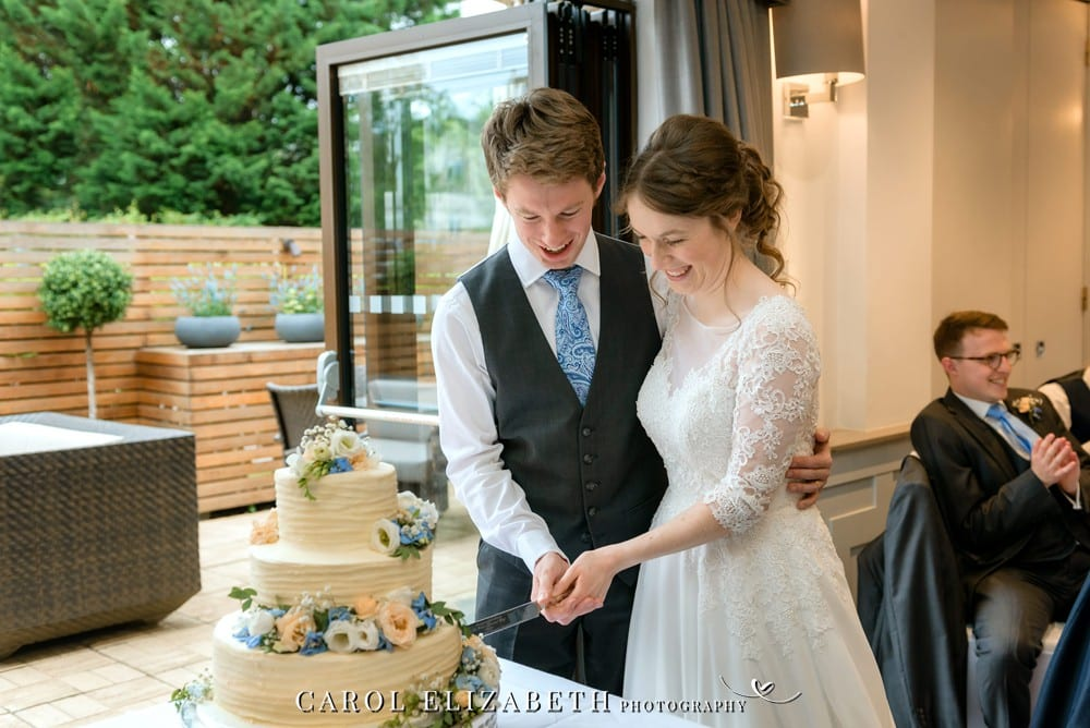Oxford wedding photographer cutting wedding cake at Voco Oxford Thames